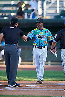 Idaho Falls Chukars manager Omar Ramirez (11) shakes hands with umpire Shin Koishizawa during the lineup exchange before a Pioneer League game against the Missoula Osprey at Melaleuca Field on August 20, 2019 in Idaho Falls, Idaho. Idaho Falls defeated Missoula 6-3. (Zachary Lucy/Four Seam Images)
