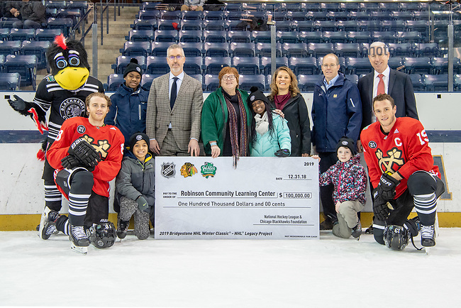December 31, 2018; Robinson Community Learning Center staff and students pose for a photo with representatives from the Chicago Blackhawks, the Chicago Blackhawks Foundation and the NHL who presented the RCLC with a $100,000 check following the Blackhawks' practice at the Compton Family Ice Arena. (Photo by Matt Cashore/University of Notre Dame)