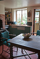 The green leather upholstery of the kitchen chairs around the gate-legged table has been chosen to tone with the paintwork of the kitchen cabinets