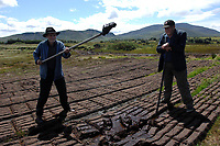 Sod it... Kerry farmers John Hoare, left and Murt O'Connor show piking rain soden turf which will not dry out this year near Glenbeigh in County Kerry on Tuesday.<br /> Picture by Don MacMonagle