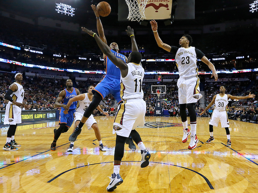 Oklahoma City Thunder guard Russell Westbrook (0) drives to the basket against New Orleans Pelicans guard Jrue Holiday (11) and forward Anthony Davis (23) during the second half of an NBA basketball game Thursday, Feb. 25, 2016, in New Orleans. The Pelicans won 123-119. (AP Photo/Jonathan Bachman)