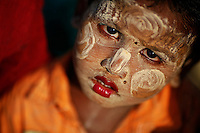 A Rohingya Muslim child wearing traditional make-up passes the time outside the tent at the camp for people displaced by violence near Sittwe April 28, 2013. Picture taken April 28, 2013.   REUTERS/Damir Sagolj (MYANMAR)