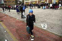 Pictured: A young boy walks alone as dozens of other migrants rest on the ground after disembarking at the port of Piraeus Friday 26 February 2016<br />