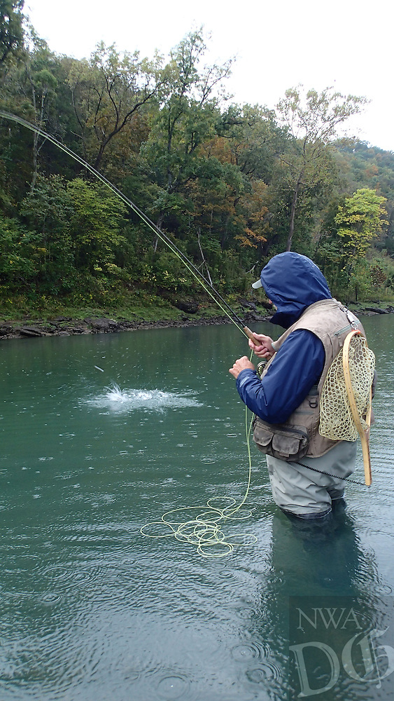 NWA Democrat-Gazette/FLIP PUTTHOFF <br /> Henderson catches a trout Oct. 8 2016 in the rain at the White River below Beaver Dam.