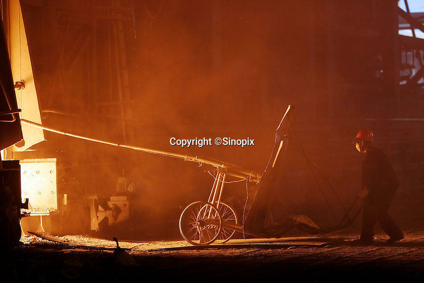A worker uses a shielded cart to retrieve samples from a steel smelter at Ma Steel (Maanshan Iron & Steel Co.) in Maanshan, Anhui Province, China..