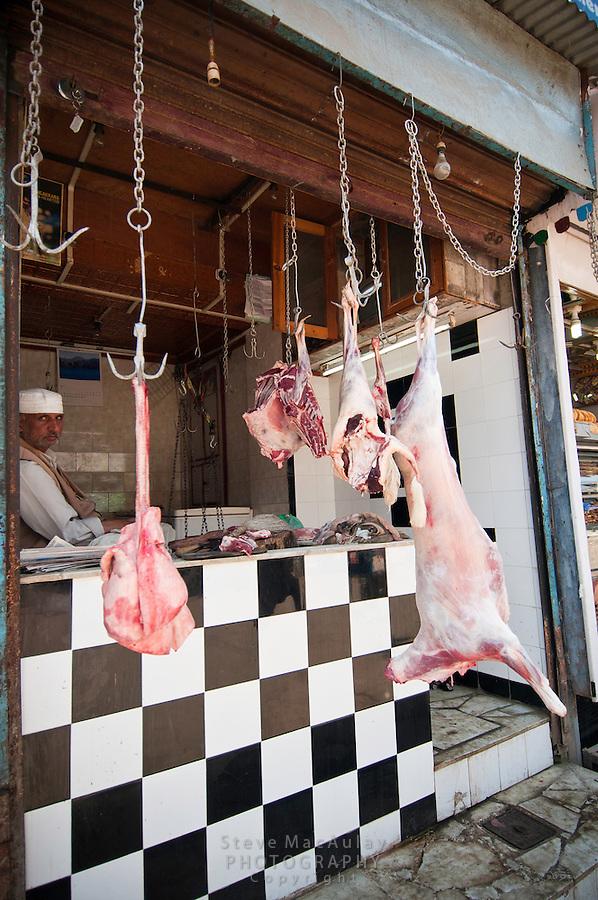 Meat market with freshly butchered lamb hanging on hooks outside shop, Srinagar, Kashmir, India.