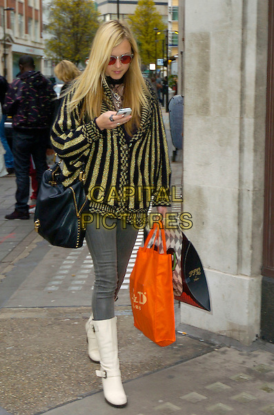 FEARNE COTTON.Leaving BBC Radio 1. She has just returned from a trip to Uganda where she was distributing mosquito nets to the poor. London, England..December 8th, 2009.full length jeans denim grey gray tucked into white boots cream yellow gold black striped stripes jacket sunglasses shades texting mobile phone bag purse hopping bags .CAP/DYL.©Dylan/Capital Pictures.