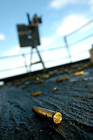 Spent shell casings cover the deck after a familiarization fire aboard USS Abraham Lincoln.