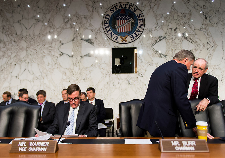 "UNITED STATES - MAY 11: From left, Sen. Mark Warner, D-Va., looks over papers as Sen. Richard Burr, R-N.C., and Sen. Jim Risch, R-Idaho,  confer before the start of the Senate (Select) Intelligence Committee hearing on ""World Wide Threats"" on Thursday, May 11, 2017. (Photo By Bill Clark/CQ Roll Call)"
