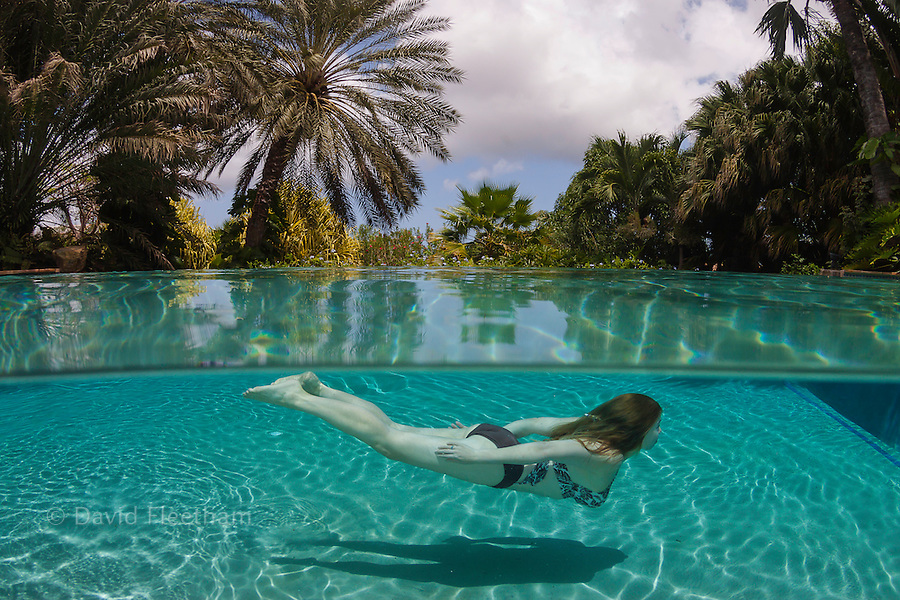 This split view of a woman (MR) underwater in a private resort pool on the island of Curacao, Netherland Antilles, Caribbean.
