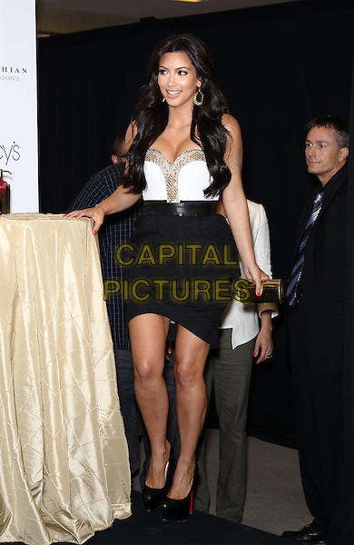 "KIM KARDASHIAN.Macy's welcomes Kim Kardashian to Fashion Show Mall to celebrate her latest fragrance ""Kim Kardashian Gold"", Las Vegas, Nevada, USA, 6th May 2011..full length strapless white bustier top skirt black dress shoes platform christian louboutin heels clutch bag gold .CAP/ADM/MJT.© MJT/AdMedia/Capital Pictures."