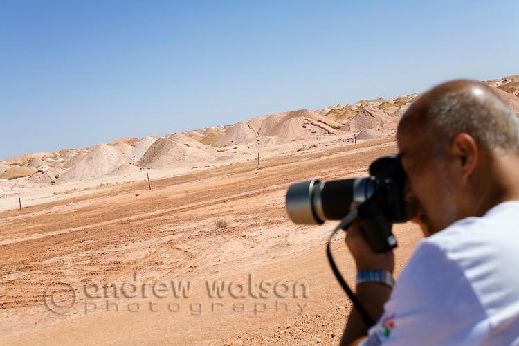 A tourist photographs the desert landscape of the Coober Pedy opal fields.   Coober Pedy, South Australia, AUSTRALIA.