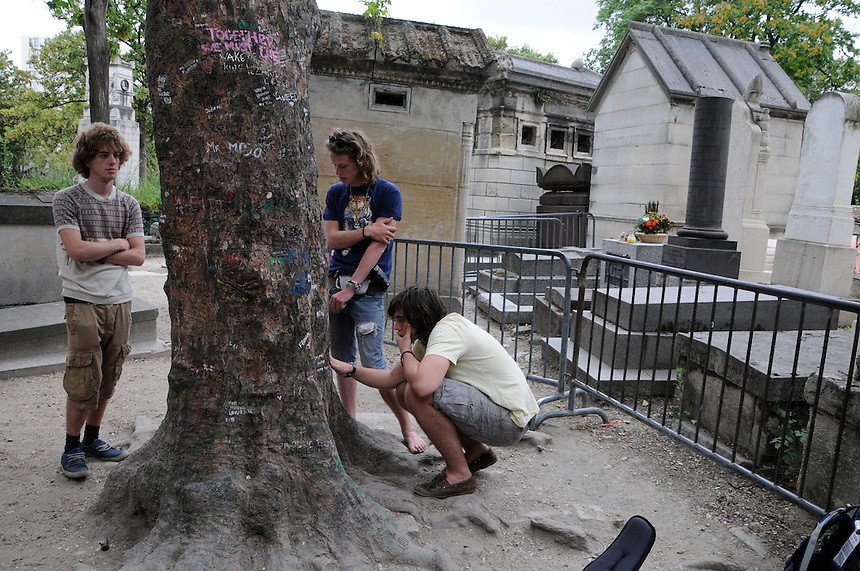 Visitors take a moment to write messages on a tree near Jim Morrison's grave at Pere Lachaise cemetery in Paris