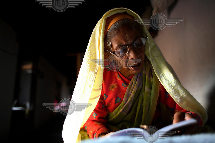 An elderly resident reads in the Pashupati Bridhashram (old peoples' home). Part of the Pashupatinath Temple complex, the old peoples' home is the largest of its type in Kathmandu, home to 140 women and 90 men. Nepal has a steadily growing elderly population.