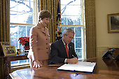 """Washington, D.C. - December 19, 2006 -- First lady Laura Bush stands by United States President George W. Bush as he signs H.R. 6143, the """"Ryan White HIV/AIDS Treatment Modernization Act of 2006,"""" which reauthorizes appropriations for and amends programs contained in the Ryan White Comprehensive AIDS Resources Emergency (CARE) Act of 1990, which provides funding for health and support services to people with HIV disease, in the Oval Office Tuesday, December 19, 2006. .Credit: Eric Draper-White House via CNP"""
