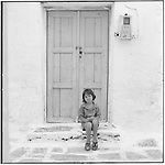 July 1996 -- Andros, Greek Islands -- A Greek girl sits in front of  a door in her local neighborhood..Andrew Kaufman©1996