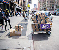 A handcart with deliveries for Amazon, Blue Apron and Jet in the New York neighborhood of Chelsea on Monday, May 23, 2016. Jet, has entered into the grocery delivery business joining AmazonFresh, Fresh Direct, Google and a litany of other e-commerce businesses that see the big bucks in groceries. (© Richard B. Levine)