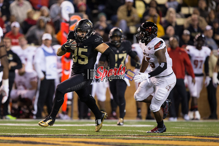 Cam Serigne (85) of the Wake Forest Demon Deacons runs away from Keith Kelsey (55) of the Louisville Cardinals after making a catch during second half action at BB&T Field on October 30, 2015 in Winston-Salem, North Carolina.  The Cardinals defeated the Demon Deacons 20-19.  (Brian Westerholt/Sports On Film)
