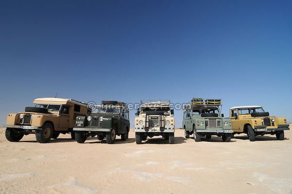 Africa, Tunisia, south of Douz. A group of five historic Series Land Rovers lined up for a journey through the desert from Douz versus Tembaine to Ksar Rhilane. --- No releases available, but releases may not be needed for certain uses. Automotive trademarks are the property of the trademark holder, authorization may be needed for some uses.  --- Info: Image belongs to a series of photographs taken on a journey to southern Tunisia in North Africa in October 2010. The trip was undertaken by 10 people driving 5 historic Series Land Rover vehicles from the 1960's and 1970's. Most of the journey's time was spent in the Sahara desert, especially in the area around Douz, Tembaine, Ksar Ghilane on the eastern edge of the Grand Erg Oriental.