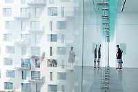 People are seen near windows at the ICA in the Seaport area of Boston, Massachusetts, USA, on Sat., July 20, 2019.