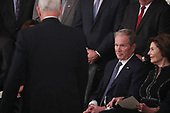 Former U.S. President George W. Bush looks up at Vice President Mike Pence as he walks back to his seat past Bush and his wife former first lady Laura Bush after Pence spoke about the president's father former President George H.W. Bush during ceremonies in the U.S. Capitol Rotunda in Washington, U.S., December 3, 2018. REUTERS/Jonathan Ernst/Pool