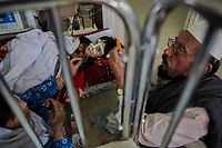 KABUL, AFGHANISTAN - SEPTEMBER 21: A mother and father work to administer medicine, on their own, for their son via a nasal tube as malnourished Afghan children receive medical care at the Indira Gandhi Children Hospital on September 21, 2013 in Kabul, Afghanistan.