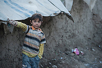 The Chamne Babrak refugee camp in Kabul 5-1-14 A boy in one of the camp streets.