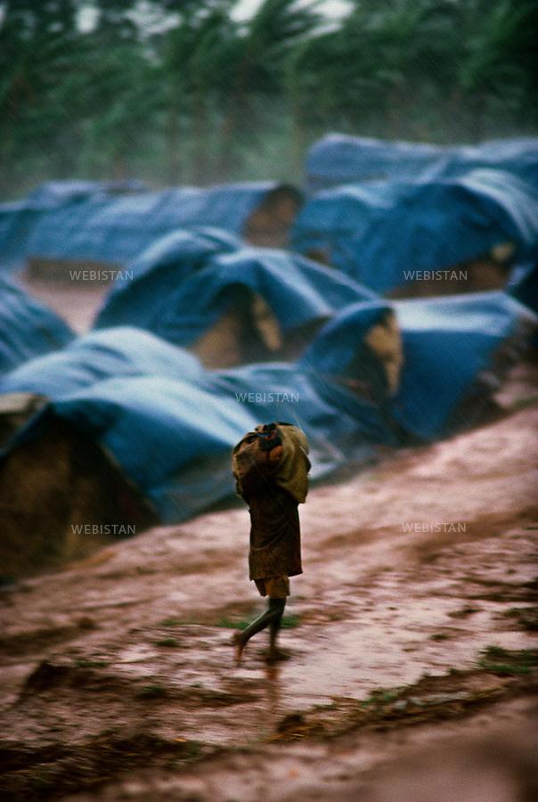 1994. Rwanda. Lake Cyohoha. Kanague Camp. During the Rwandan Genocide, in a refugee camp, an orphan Burundian Hutu boy runs under the rain in the middle of the tents. Rwanda. Lac Cyohoha. Camp Kanague. Pendant le génocide au Rwanda, dans un camp de réfugiés, un orphelin hutu burundais court sous la pluie au milieu des tentes.