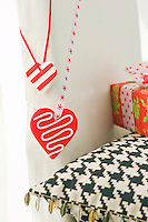 A pair of red and white hearts on lengths of ribbon are suspended over the back of a contemporary white chair