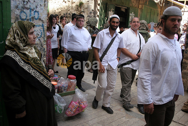 Palestinian woman looks at a group of Jewish settlers gather in the city center of the West Bank town of Hebron on May 08, 2010. photo by Najeh Hashlamoun
