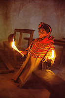 Indian woman praying holding candles in church of San Mateo Ixtatan, Cuchumatanes Mountains, Guatemala<br />