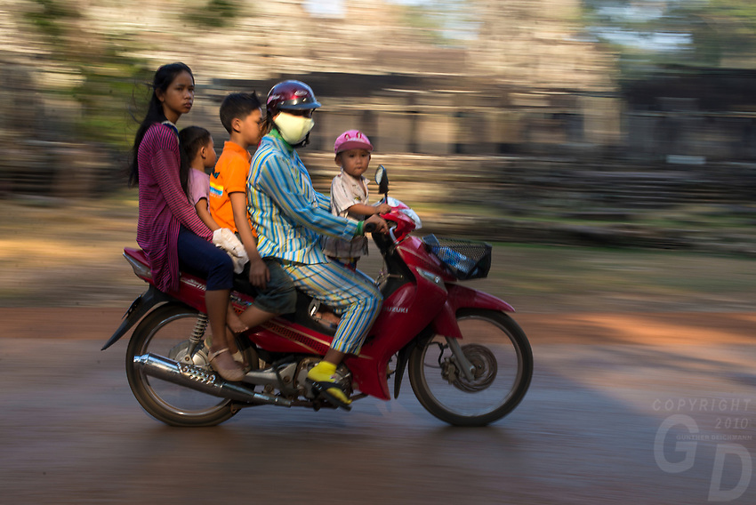 A local Khmer family of 5 all crowded on a small scooter. Activity near he popular Bayon temple ruins