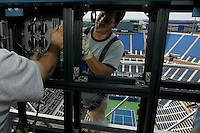 Flushing, NY - 18 August 2005 - Workers install the giant electronic score board overlooking the Arthur Ash court at the National Tennis Center in Flushing, Queens, NY, USA, during preparations for the 2005 US Open, 18 August 2005.
