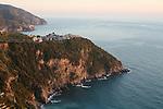 Village de Corniglia perche sur une pointe rocheuse (au loin le village de Manarola dominant la mer) Parc national des Cinque Terre. Ligurie. Italie.