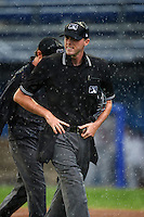 Umpire Brandin Sheeler watches the grounds crew pull the tarp during a game between the Mahoning Valley Scrappers and Batavia Muckdogs on July 1, 2015 at Dwyer Stadium in Batavia, New York.  The game was postponed due to rain.  (Mike Janes/Four Seam Images)