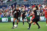 USWNT midfielder Carli Lloyd (10) looking at passing the ball to Lauren Chesney.