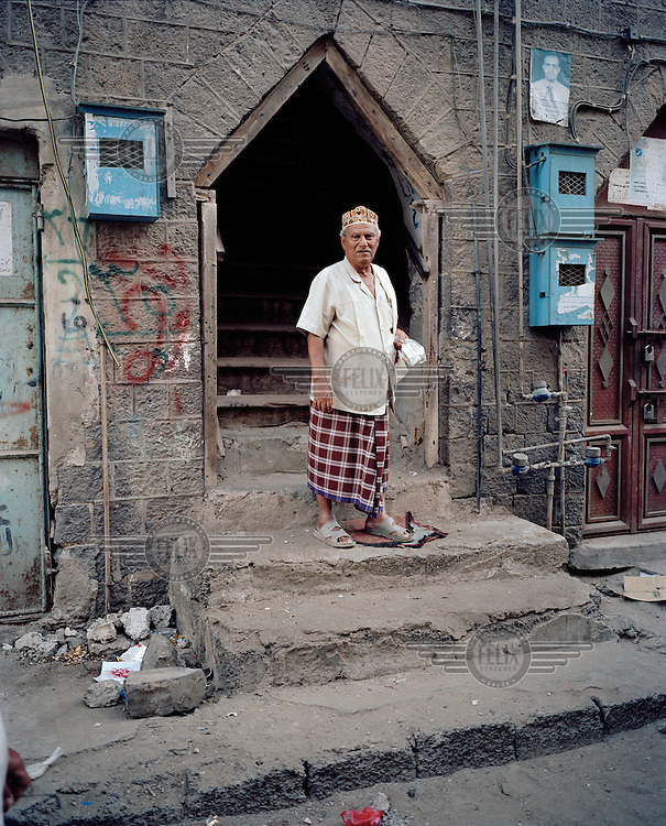 Abdul Essa stands in the doorway of his apartment building. The triangular shaped doorway is an unusual feature..