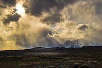 The sun starts to break through storm clouds over the Torres Del Paine massive, Patagonia Chile.