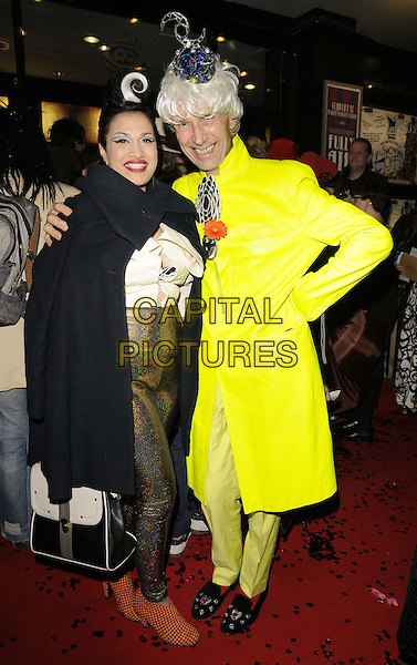 "guest & Andrew Logan.The ""The Briish Guide To Showing Off"" UK premiere, Prince Charles cinema, Leicester Place, London, England..November 6th, 2011.full length yellow green jacket neon fluorescent hand on hip black cape trousers gold wig.CAP/CAN.©Can Nguyen/Capital Pictures."