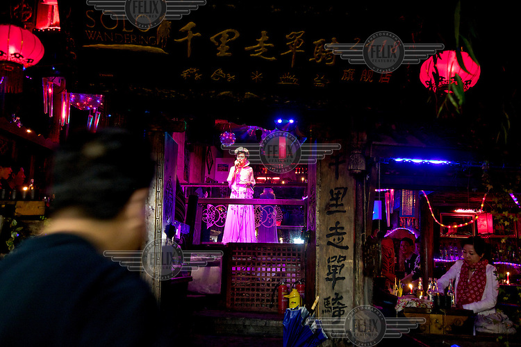 A woman sings regional folk songs in a restuarant in Lijiang a town whose historic buildings are a major tourist attraction and an UNESCO World Heritage Site. /Felix Features