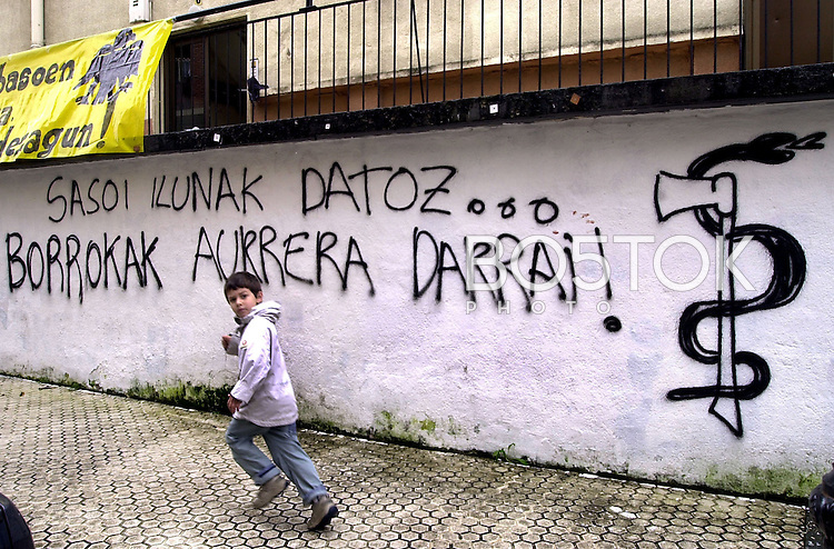 "A boy runs past a graffiti reading in Basque ""Dark times come, the fight continues"" on  August 26, 2002, in the Basque town of Ibarra, Basque Country. (Ander Gillenea / Bostok Photo)"