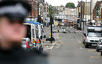 PH: Rick Findler..07.08.11 Police stand in front of the carnage caused by rioting on Tottenham High Road that saw 26 officers injured. The violence was sparked by the fatal shooting of Mark Duggan by a police officer on thursday night.