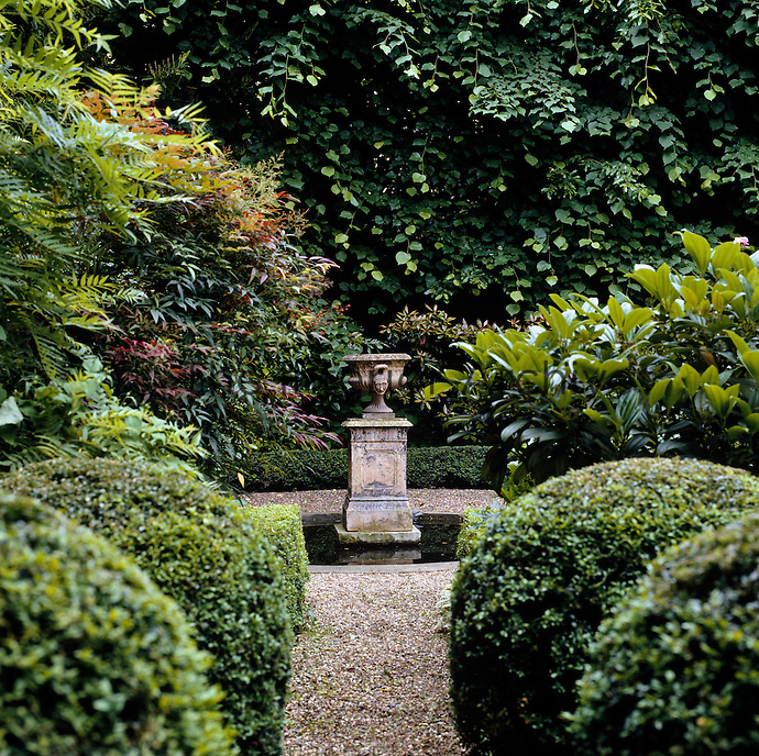 View down a path bordered with box hedging towards a stone urn on a plinth in the centre of the ornamental pond
