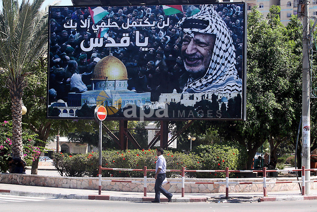 A Palestinian man walks near a big banner for the late Palestinian leader Yasser Arafat in Gaza City, on Sep. 15, 2011 as the Palestinians prepare to submit a formal request to become the 194th member of the United Nations when the General Assembly begins its meetings on September 20, despite US and Israeli opposition. Palestinian officials have said that the bid for UN statehood recognition does not run counter to any willingness to negotiate, and is aimed at achieving a just peace. Israel and the US however say a Palestinian state can only come into being through negotiations, and not through any unilateral move. Photo by Mohammed Asad