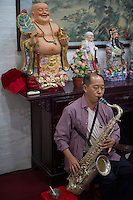 An amateur musician of the Huang Cantonese Opera group plays saxophone during practice at the ancestral temple at Yanbu Village in Nanhai district of Foshan city, Guangdong province, November 8, 2011.