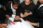 Palestinian relatives gather around the body of Raed El-Bor at the morgue of AL-shifa hospital in Gaza city, April 9, 2011.The Israeli army pounded the Gaza Strip, killing at least 18 people while militants fired dozens of mortars and rockets into southern Israel in the deadliest 24 hours of violence since a devastating war ended more than two years ago. Photo by Mohammed Asad