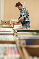 STAFF PHOTO ANTHONY REYES &bull; @NWATONYR<br /> Ron Welker, volunteer with the Springdale Public Library, sorts and stacks books Monday, Sept. 22, 2014 for the Springdale Public Library's annual book sale. The sale will be Wednesday through Saturday during regular library hours. All money from the event will benefit the library and various library programs.