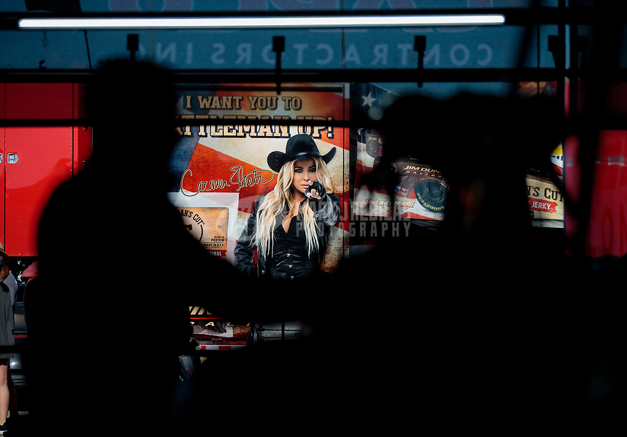 Apr 14, 2019; Baytown, TX, USA; An advertisement with Carmen Electra is visible behind a crew member for NHRA top fuel driver Steve Torrence during the Springnationals at Houston Raceway Park. Mandatory Credit: Mark J. Rebilas-USA TODAY Sports