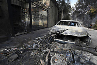 Pictured: A car destroyed in the blaze near the forest in the aftermath of the wild forest fires in the Neos Voutzas area near Rafina, Greece. Tuesday 24 July 2018<br /> Re: Deaths caused by wild forest fires throughout Greece.