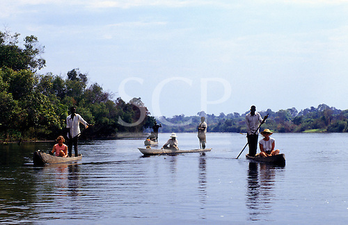 Zambia. Zambian men in dug out canoes, each with a tourist passenger.